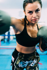 Portrait of female boxer throwing punch - CUF48242