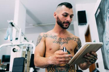 Man checking notepad in gym - CUF48245