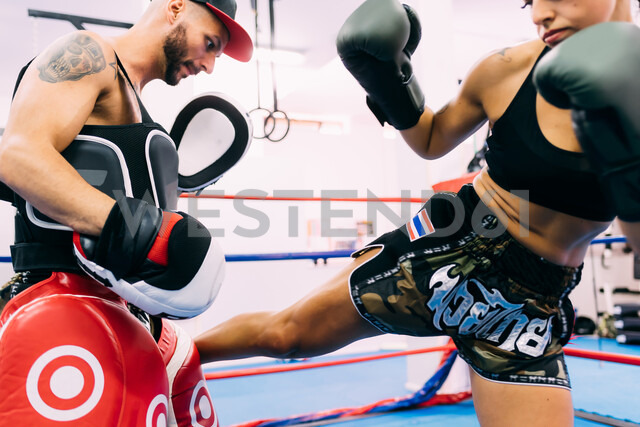Male and female boxers working out in boxing ring - CUF48248