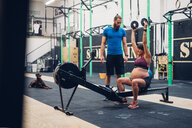 Trainer guiding pregnant woman using weights in gym - CUF48254