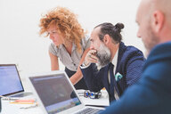 Businesswoman and men looking at laptop on office desk, over shoulder view - CUF48260