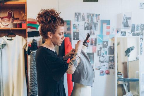 Fashion designer pinning garment onto dressmaker's dummy - CUF48266