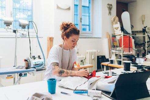 Fashion designer working in her studio - CUF48275