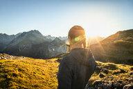 Hiker taking break with warm drink, Karwendel region, Hinterriss, Tirol, Austria - CUF48302