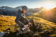 Hiker taking break with warm drink, Karwendel region, Hinterriss, Tirol, Austria - CUF48305