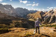 Hiker and pet dog enjoying view, Karwendel region, Hinterriss, Tirol, Austria - CUF48314