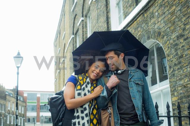 Happy couple under umbrella in street, London, UK - CUF48326