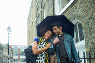 Happy couple under umbrella in street, London, UK - CUF48326