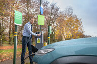 Man charging electric car at charge point, Manchester, UK - CUF48329