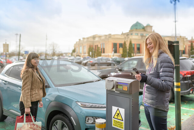 Female shoppers charging electric car at charge point, Manchester, UK - CUF48332