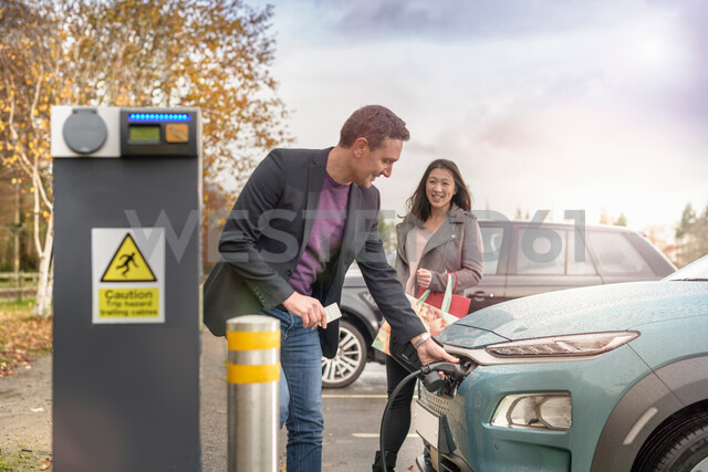 Man and woman charging electric car at car charging park, Manchester, UK - CUF48335