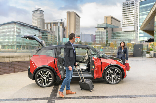 Man and woman with parked electric car, Manchester, UK - CUF48338 - Monty Rakusen/Westend61