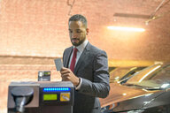 Businessman using access card at electric vehicle charging station, Manchester, UK - CUF48344