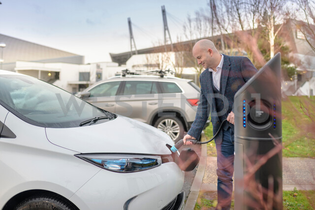 Businessman plugging in electric car at charging point, Manchester, UK - CUF48347 - Monty Rakusen/Westend61