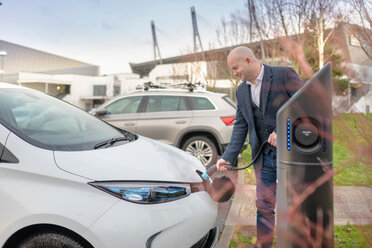 Businessman plugging in electric car at charging point, Manchester, UK - CUF48347