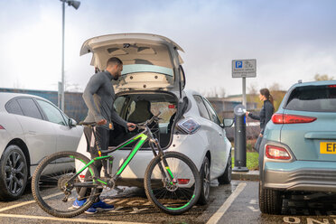 Man and woman with mountain bike at electric car charging point, Manchester, UK - CUF48350