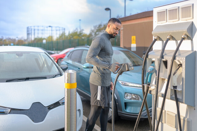 Sportsman at electric car charging point, Manchester, UK - CUF48353 - Monty Rakusen/Westend61