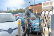Sportsman at electric car charging point, Manchester, UK - CUF48353