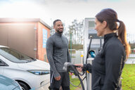 Sportsman and woman charging electric car at charging bay, Manchester, UK - CUF48356