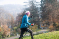 Senior woman nordic walking in park - CUF48359