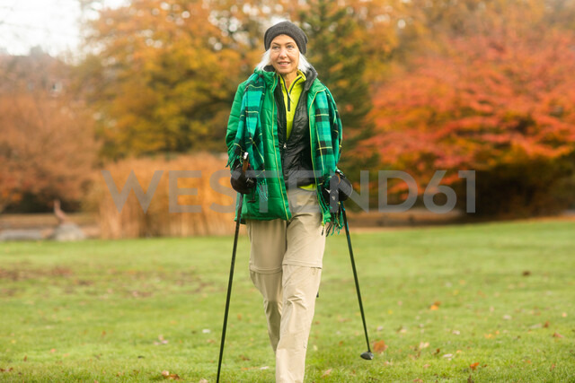 Mature woman nordic walking in park - CUF48374