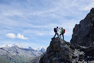 Hikers high fiving on peak of rock, Mont Cervin, Matterhorn, Valais, Switzerland - CUF48383