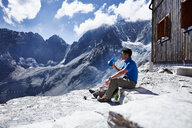 Hiker drinking from water bottle, Mont Cervin, Matterhorn, Valais, Switzerland - CUF48395