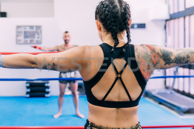 Male and female boxers working out in boxing ring - CUF48398