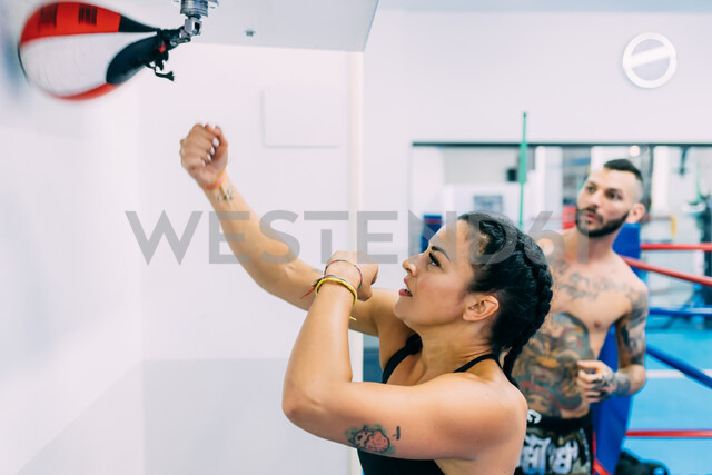 Woman using punch bag in gym - CUF48407