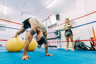 Male and female boxers working out in boxing ring - CUF48416
