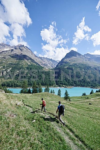 Hikers on lush green field, lake in background, Mont Cervin, Matterhorn, Valais, Switzerland - CUF48419