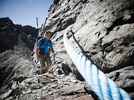 Hiker using rope to ascend rock face, Mont Cervin, Matterhorn, Valais, Switzerland - CUF48428