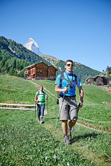 Hikers on lush green field, chalets in background, Mont Cervin, Matterhorn, Valais, Switzerland - CUF48434