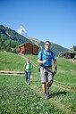 Hikers on lush green field, chalets in background, Mont Cervin, Matterhorn, Valais, Switzerland - CUF48434