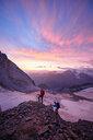 Hikers climbing rock at sunset, Mont Cervin, Matterhorn, Valais, Switzerland - CUF48446
