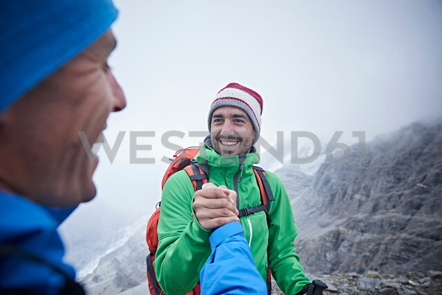 Hikers congratulating themselves, Mont Cervin, Matterhorn, Valais, Switzerland - CUF48452
