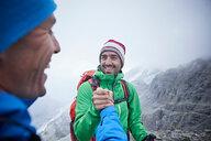 Hikers congratulating themselves, Mont Cervin, Matterhorn, Valais, Switzerland - CUF48452