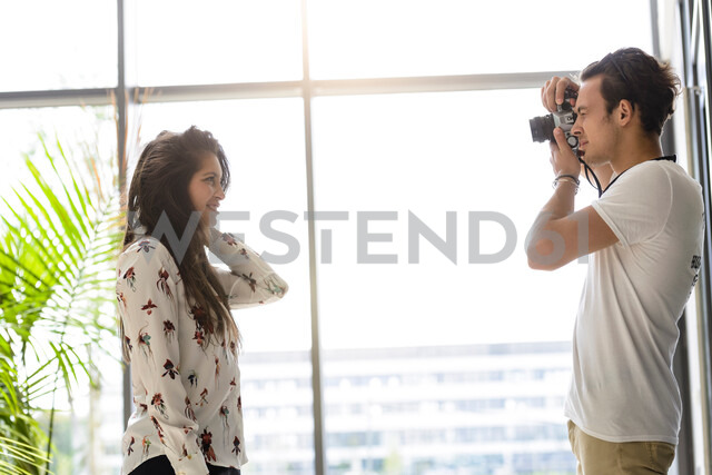 Colleagues taking photo by glass wall - CUF48455