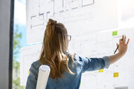 Woman contemplating plans on glass wall - CUF48479