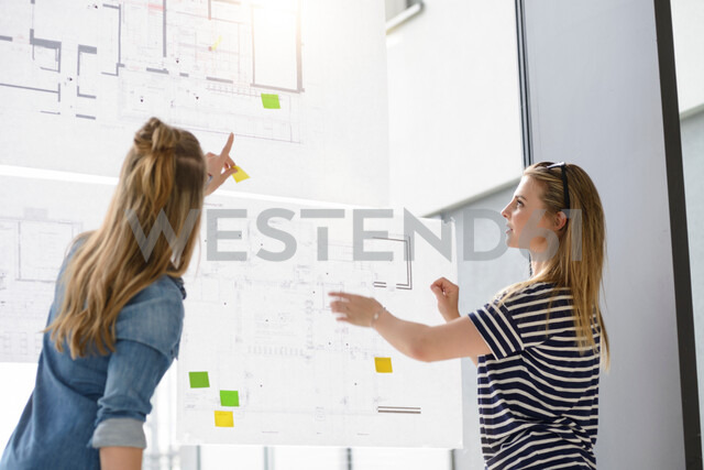 Colleagues discussing plans on glass wall - CUF48482