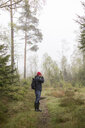 Mid adult man in a misty forest in Lerum, Sweden - FOLF10253
