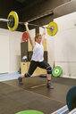 Young woman lifting a barbell in a gym - FOLF10271