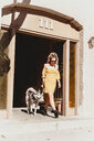 Young woman with pet dog at entrance of building - ISF20128