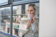 Businesswoman taking coffee break in office - ISF20158