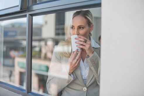 Businesswoman taking coffee break in office - ISF20158
