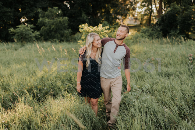 Romantic young woman and boyfriend strolling in field of long grass - ISF20170