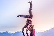 Two young women practicing acroyoga in front of mountain range at sunset, Squamish, British Columbia, Canada - ISF20194