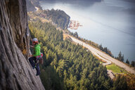 Young female rock climber climbing rock face, elevated view, The Chief, Squamish, British Columbia, Canada - ISF20197