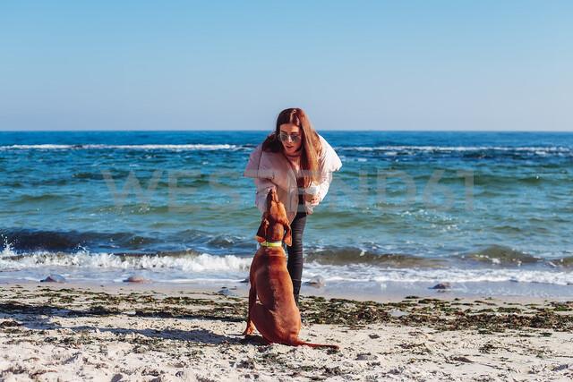 Stylish mid adult woman on beach petting her dog, Odessa, Odeska Oblast, Ukraine - ISF20206
