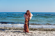 Stylish mid adult woman on beach petting her dog, Odessa, Odeska Oblast, Ukraine - ISF20206